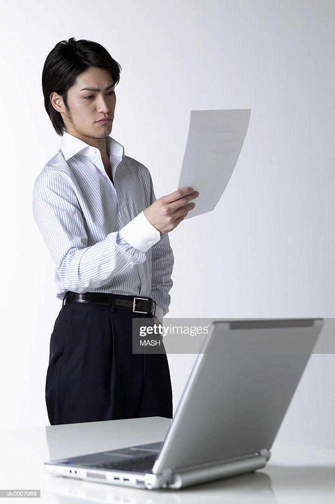 Businessman Looking at a Document With a Laptop in the Foreground : Stock Photo