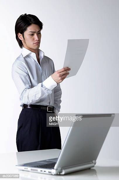 businessman looking at a document with a laptop in the foreground - オープンネック ストックフォトと画像
