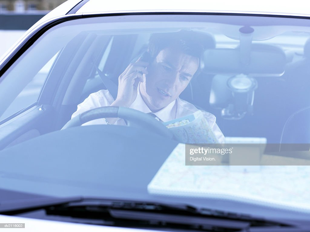 Businessman Looking at a Map and Using a Mobile Phone in His Car : Stock Photo