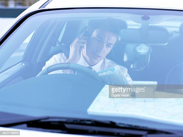 Businessman Looking at a Map and Using a Mobile Phone in His Car