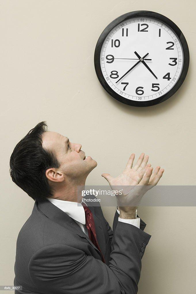 Businessman looking at a wall clock : Foto de stock