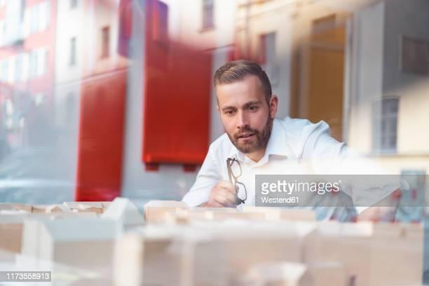 businessman looking at architectural model in office - architekturberuf stock-fotos und bilder