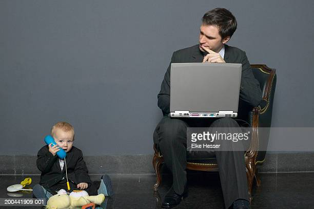 Businessman looking at baby son (18-24 months) using toy phone