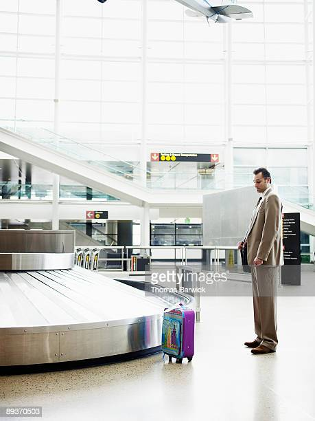 Businessman looking at bag at baggage claim