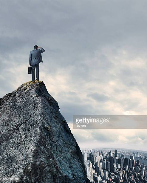 Businessman Looking At Big City While Standing On Mountain Top