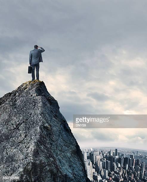 Empresário olhando para a grande cidade de pé no topo da montanha ao