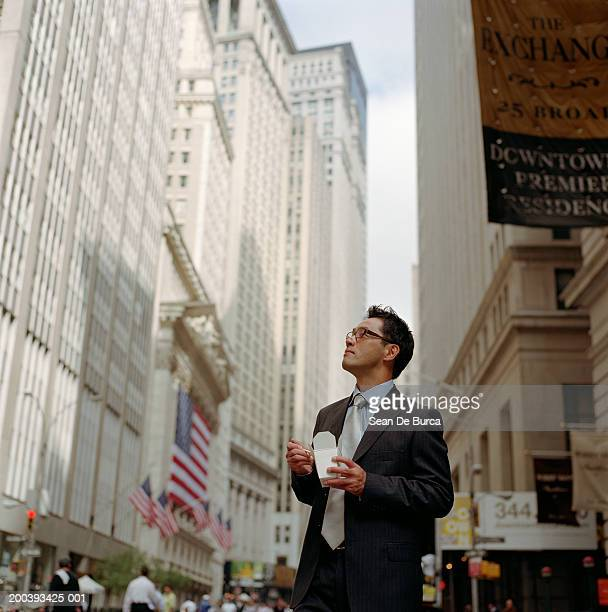 Businessman looking at building, eating food with chopsticks