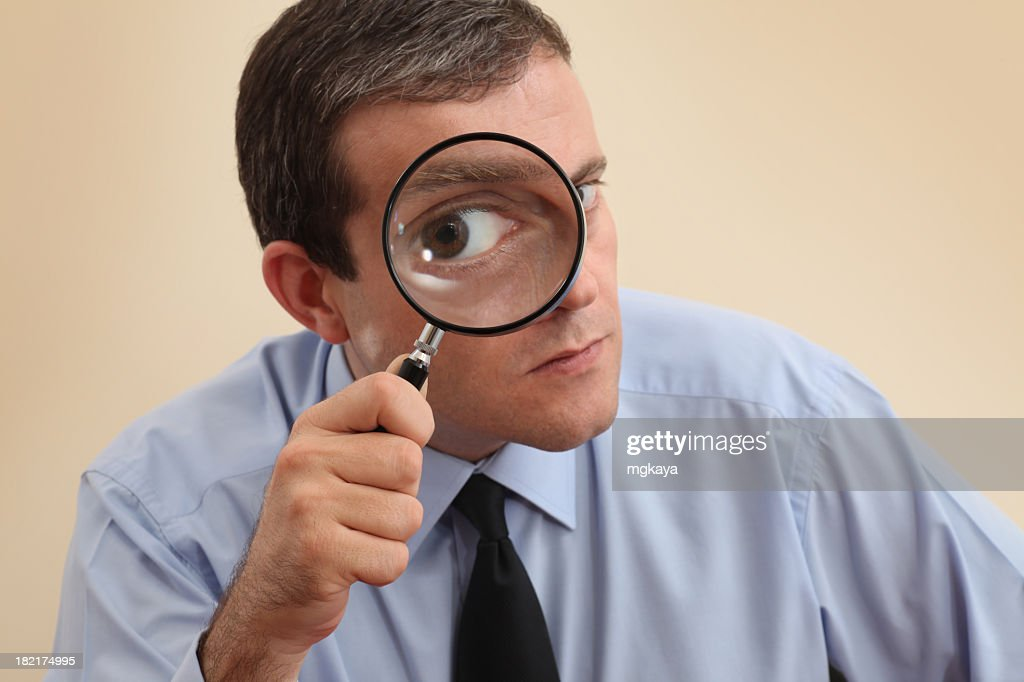 Businessman looking at camera through a magnifying glass : Stock Photo