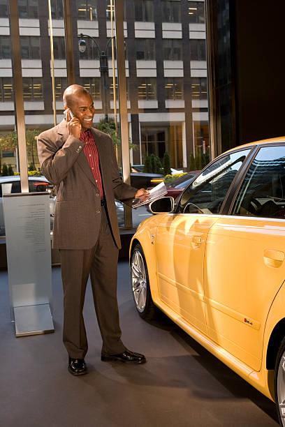 Businessman looking at car in showroom, using mobile phone