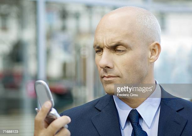 Businessman looking at cell phone, furrowing brow