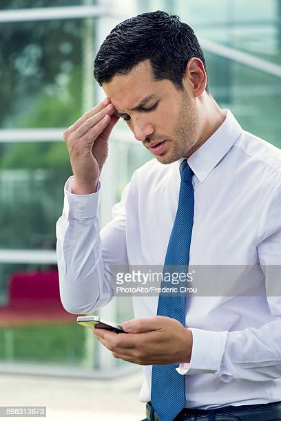 Businessman looking at cell phone with worried expression