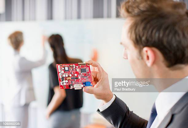 Businessman looking at circuit board in office