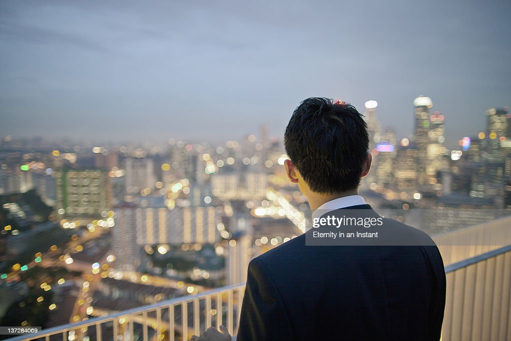Businessman looking at city at dusk : Stock Photo