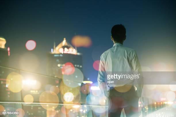 Businessman looking at city at night