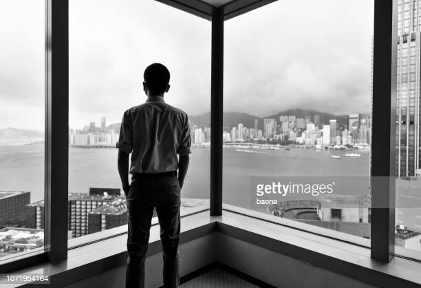 businessman looking at city through office window - corner stock pictures, royalty-free photos & images