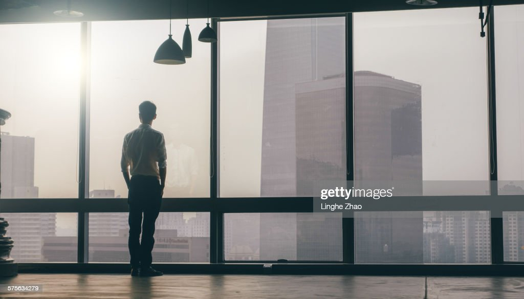 Businessman looking at cityscape from office : Stock Photo