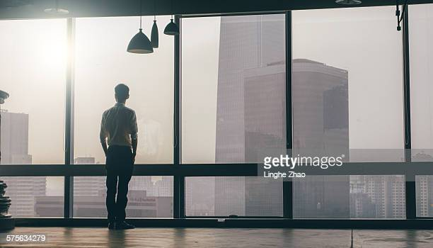 businessman looking at cityscape from office - skyscraper imagens e fotografias de stock