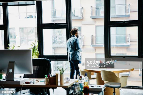 Businessman looking at cityscape outside office window