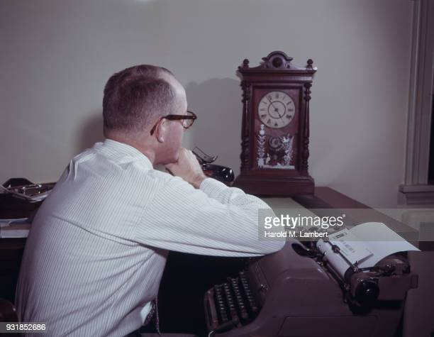 Businessman looking at clock in office