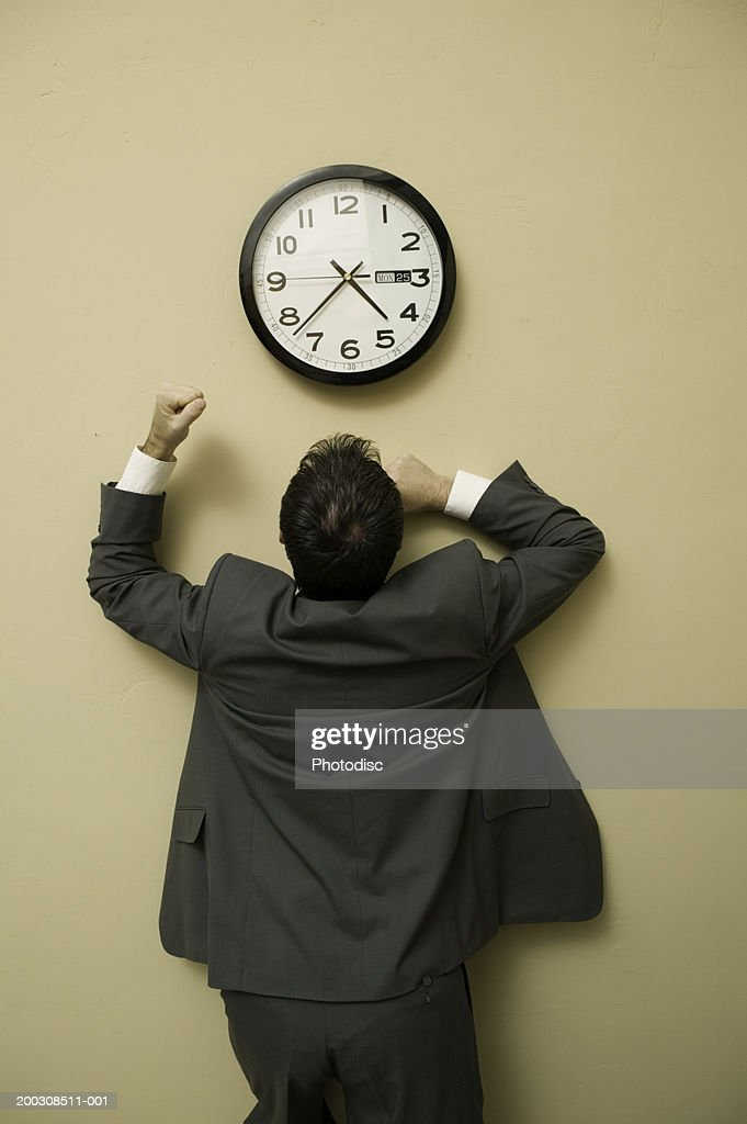 businessman looking at clock punching wall portrait ストックフォト
