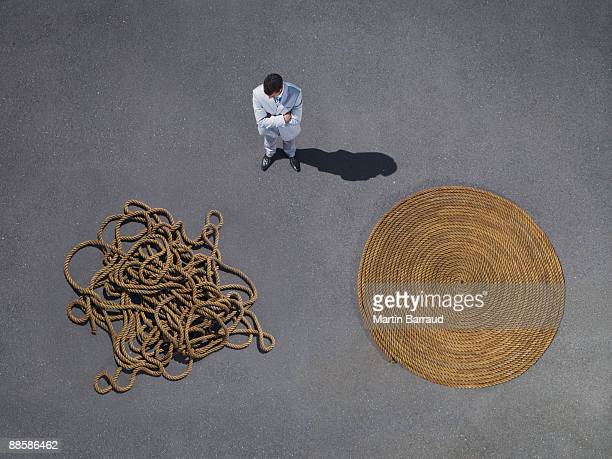 Businessman looking at coiled and tangled rope