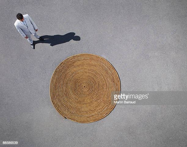 Businessman looking at coiled rope