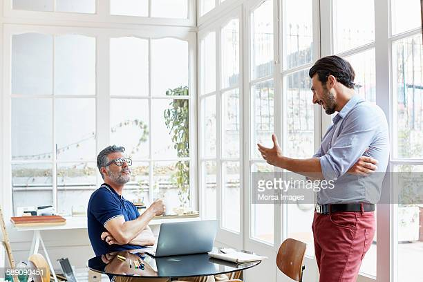 Businessman looking at colleague gesturing