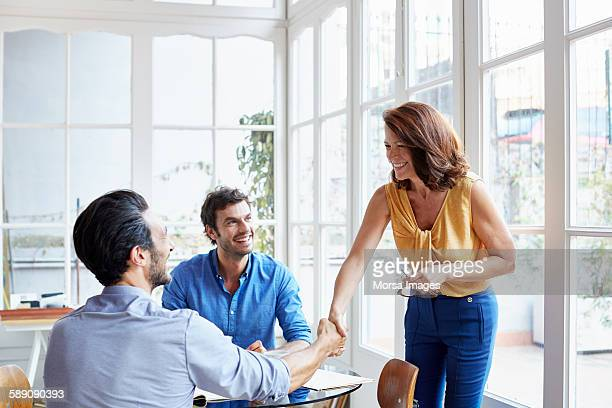 Businessman looking at colleagues making handshake