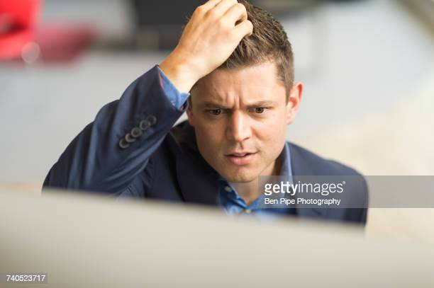 Businessman looking at computer in office scratching his head