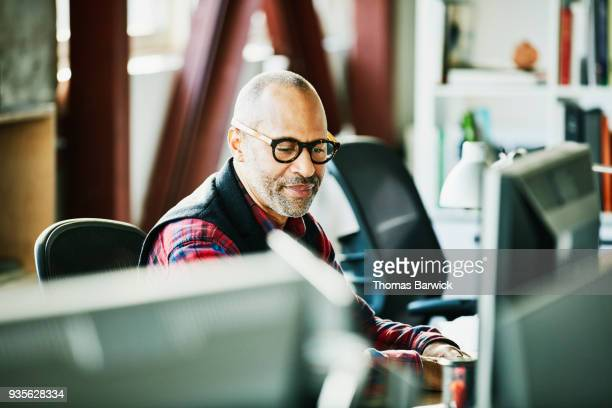 Businessman looking at computer monitor at workstation in design office