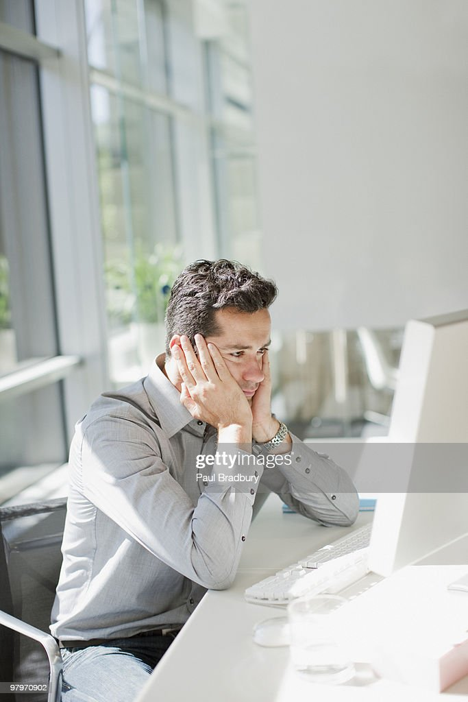 Businessman looking at computer with head in hands : Stock Photo