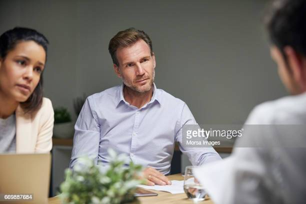 Businessman looking at coworker in textile factory