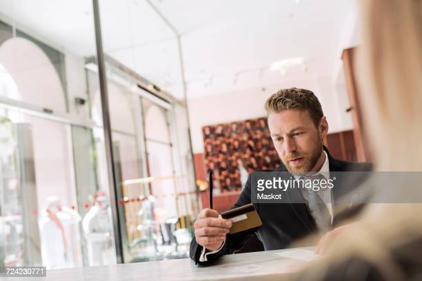 Businessman looking at credit card in hotel reception