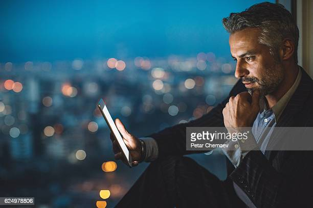 businessman looking at digital tablet at night - 知能 ストックフォトと画像