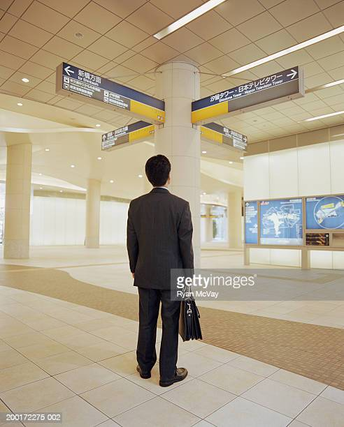 Businessman looking at directional signs in subway station, rear view
