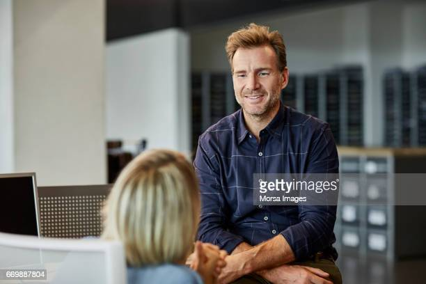Businessman looking at female colleague in office