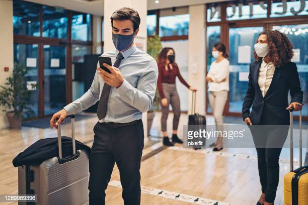 businessman looking at his cell phone while waiting in line at the hotel reception - reopening stock pictures, royalty-free photos & images