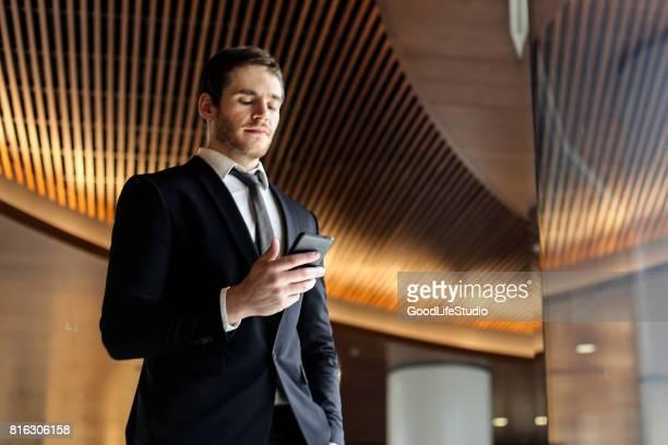 zakenman kijken naar zijn mobiele telefoon - mobile stockfoto's en -beelden
