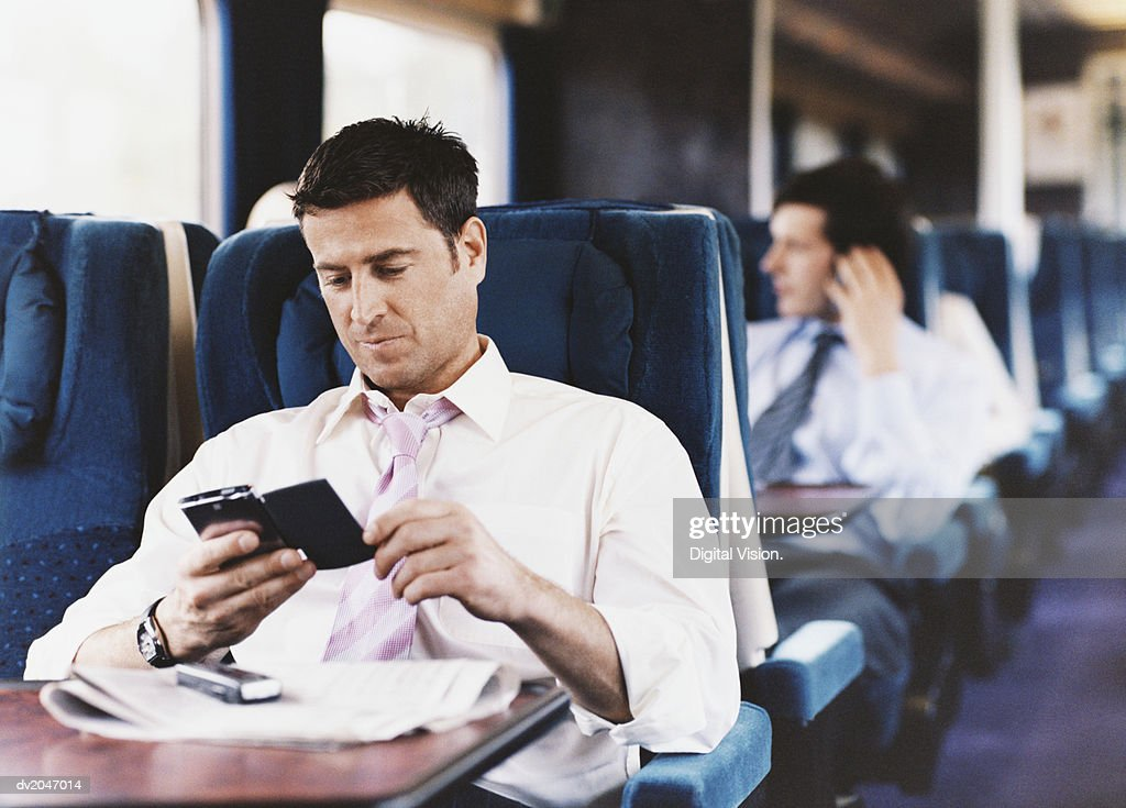 Businessman Looking at His PDA on a Passenger Train : Stock Photo
