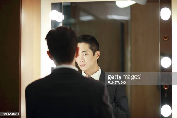Businessman looking at his reflection in mirror