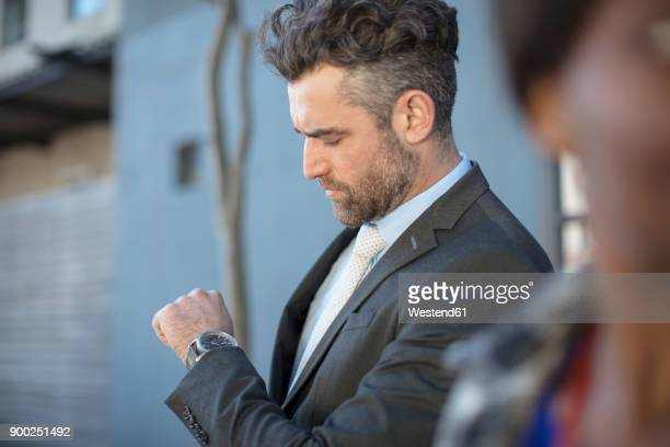 businessman looking at his watch outdoors - time management stock photos and pictures