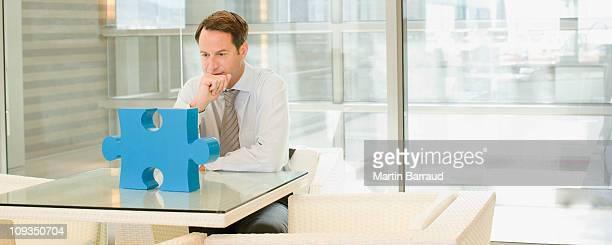 businessman looking at jigsaw puzzle piece - alleen één mid volwassen man stockfoto's en -beelden