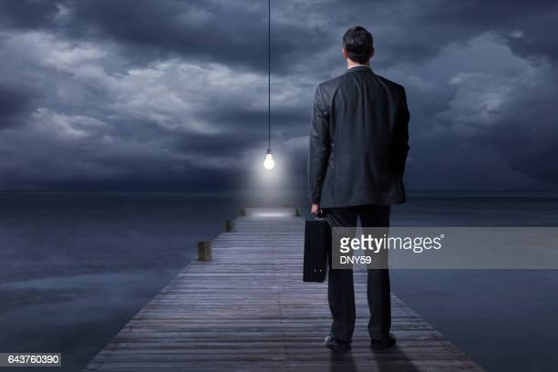 Businessman Looking At Light Bulb At End Of Pier