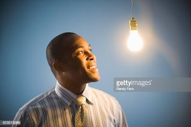 Businessman Looking at Lightbulb