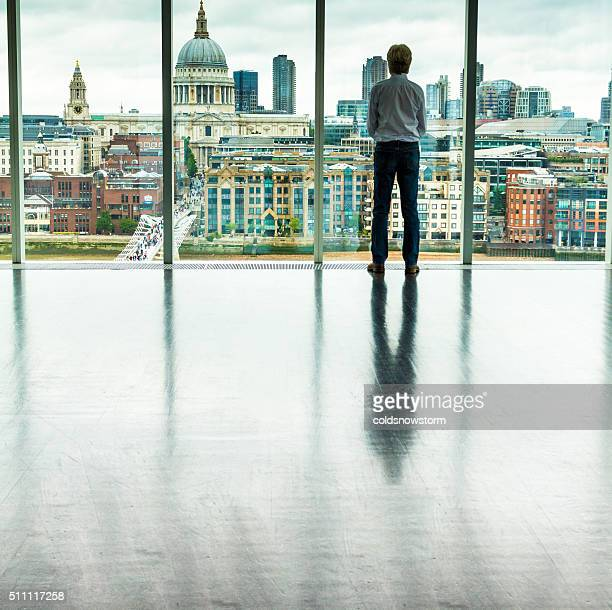 Businessman Looking at London City Skyline from Office Window