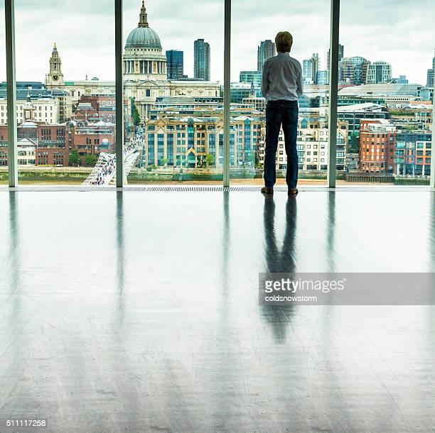Geschäftsmann schaut an Skyline von London von Office-Fenster