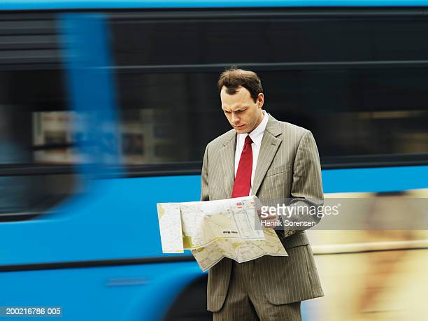 Businessman looking at map on street, bus passing in background