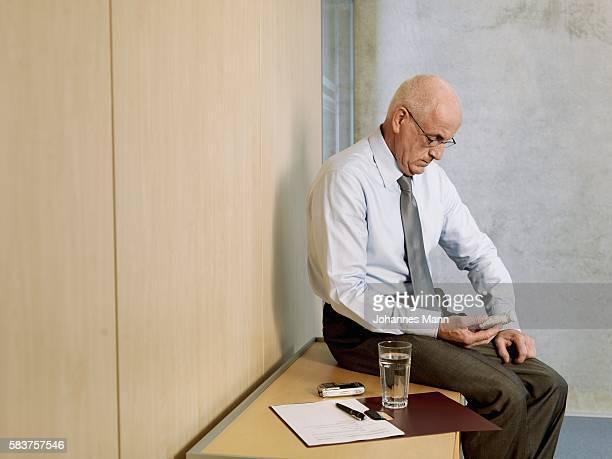 Businessman looking at medicine bottle
