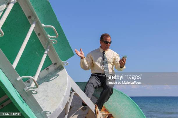 businessman looking at mobile phone drifting on a buoy out at sea - hand sign stock pictures, royalty-free photos & images