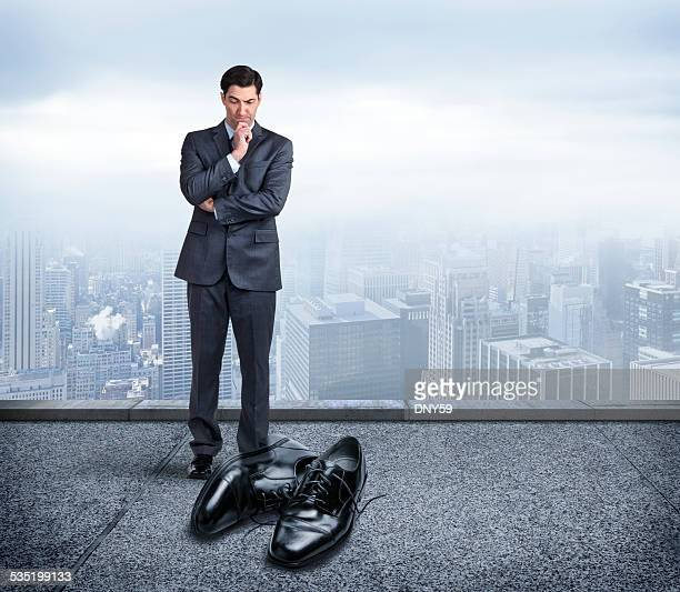 Businessman Looking At Pair Of Big Shoes To Fill